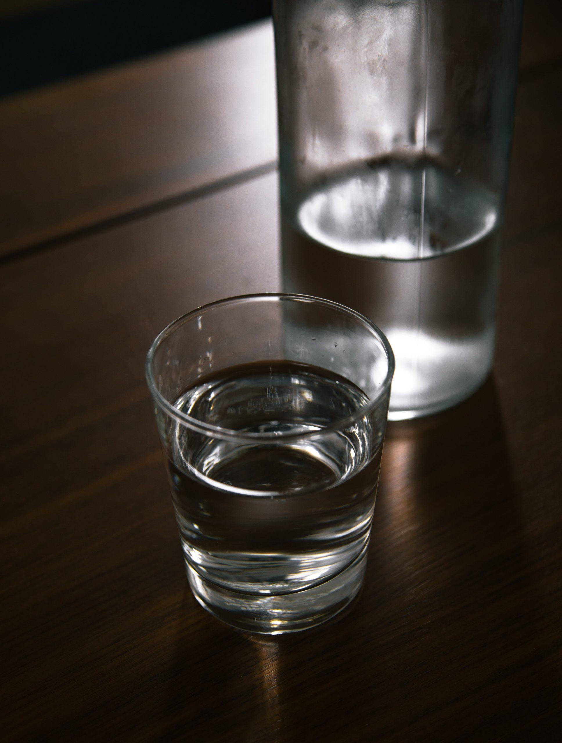 Imagem de um copo e uma garrafa com água
