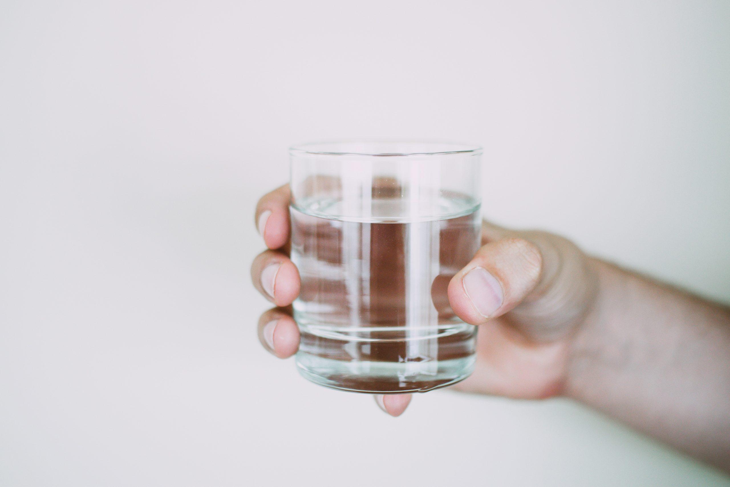 Mão segurando um copo com água